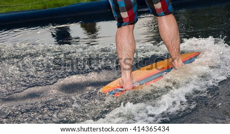 Man riding a small surfboard or foot board along an outdoor water slide set up on a green lawn, low angle of his lower legs - stock photo