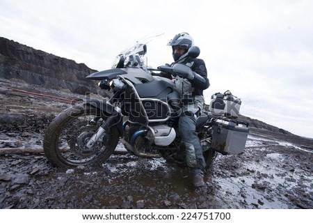Man Riding Adventure Motorcycle Stuck In Mud - stock photo