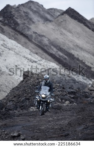 Man Riding Adventure Motorcycle Through Mud Off road - stock photo