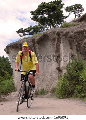 Man riding bicycle in a rocky area.