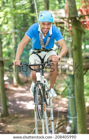 Man riding bicycle on tightrope at high rope course - stock photo