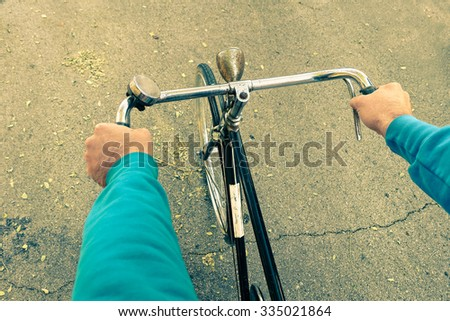 Man riding bike - Male hands on vintage bicycle on the road - Cyclist guy on alternative transportation - Student arms on retro vehicle - Green concept of environment preservation and  energy saving - stock photo
