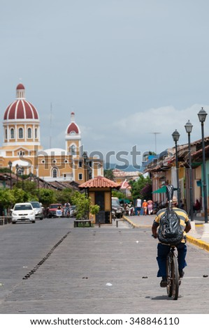 Man riding bike on street in city Granada, Nicaragua, Central America