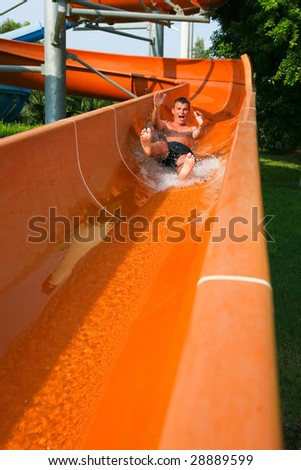 Man riding down a water slide - stock photo