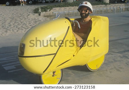 Man riding futuristic bicycle along beach - stock photo