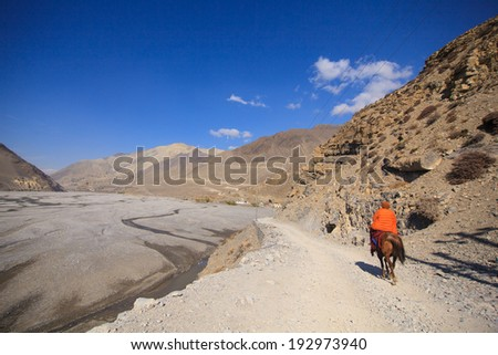Man riding Horse with Himalayan background  - stock photo