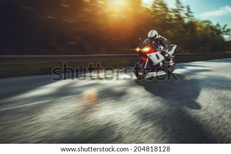 man riding motorcycle in asphalt road - stock photo