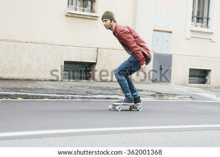 man riding on a skate in the city street , motion effect panning - stock photo