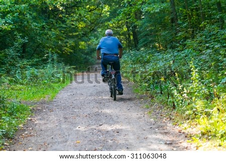 Man riding on bike through summertime forest. Forest path with man riding on bike.