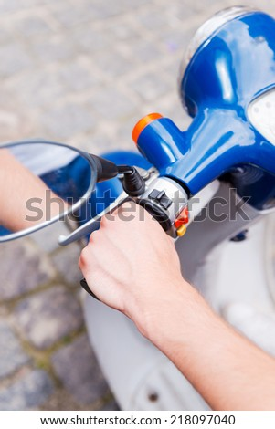 Man riding scooter. Close-up of man riding scooter along the street - stock photo