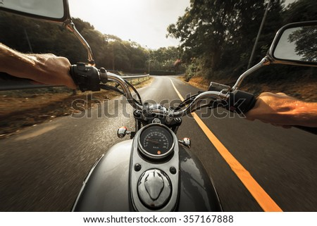 Man riding the motorcycle on the empty asphalt road through the forest - stock photo