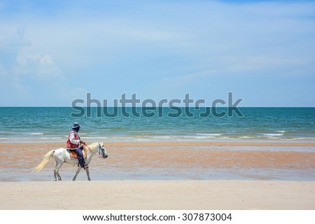 Man riding the white horse on the beach among beautiful seascape of Huahin, Thailand - stock photo