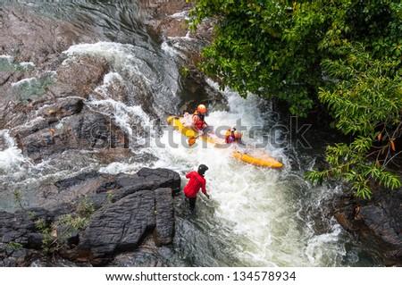 Man riding whitewater rapids in his Kayak ,Thailand - stock photo