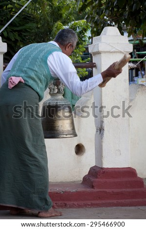 Man ringing the bell in Bagan,Myanmar February 14, 2013  - stock photo