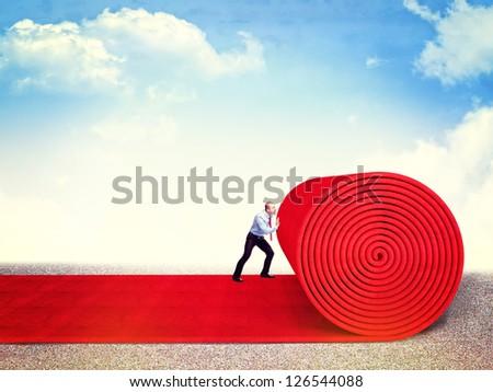 man roll huge red carpet - stock photo