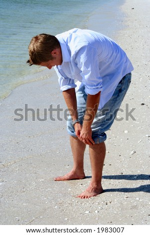 Man rolling jeans for a wade in sea