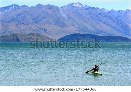 Man rows a kayak over a lake with mountain in the background.  - stock photo