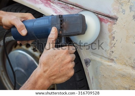 man rub away rust from an old car with a grinder machine - stock photo