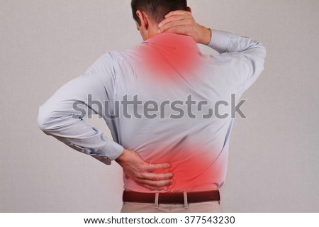 Man rubbing his painful back close up. Business man holding his lower back. Pain relief concept  - stock photo