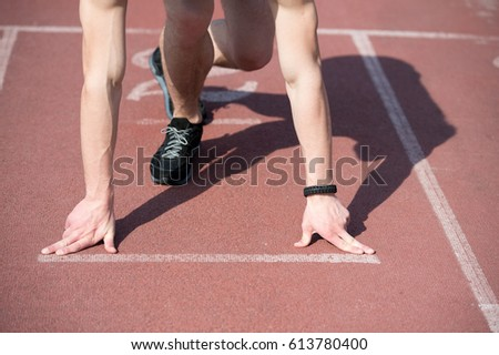 man runner, athletic guy with muscular hands and legs start on running track or treadmill in black fashion shoes sunny outdoor. summer activity and sport. healthy lifestyle, competition, challenge