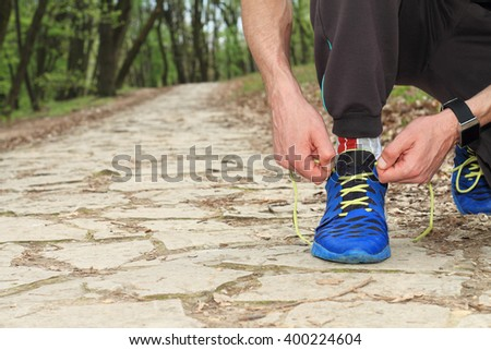 Man runner getting ready for jogging. Sport, active lifestyle concept. Fitness people using smart watch.