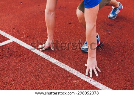 Man runner in blue shirt and shorts and sport shoes in steady position before run at start of race track preparing for run on a stadium unrecognizable no face focus on hands - stock photo