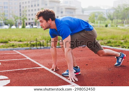 Man runner in blue shirt and shorts and sport shoes in steady position before run at start of race track preparing for run on a stadium perspective view with university campus on background - stock photo