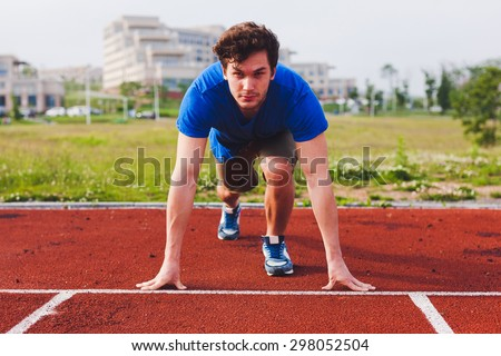 Man runner in blue shirt and shorts and sport shoes in steady position before run at start of race track preparing for run on a stadium with university campus on background - stock photo