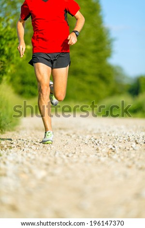 Man runner running on country road in summer sunset. Young athlete male cross country training and doing workout outdoors in green nature, summer blue sky - stock photo