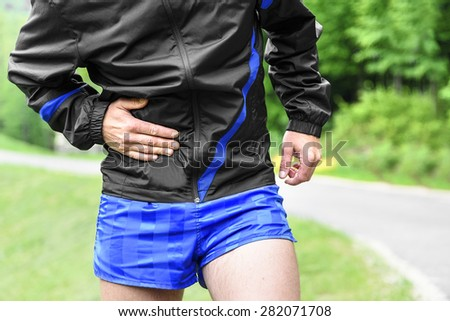 Man runner side cramps after running outdoors - stock photo