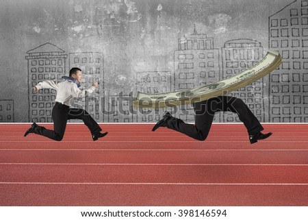Man running after money with human legs, on red running track with city skyline background. - stock photo