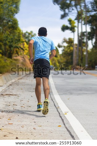 man running along the asphalt road - stock photo