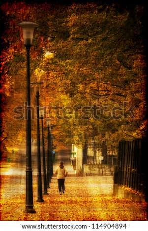 Man running at alley in autumn park. Photo in old image style. - stock photo