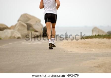 Man running at the beach - stock photo