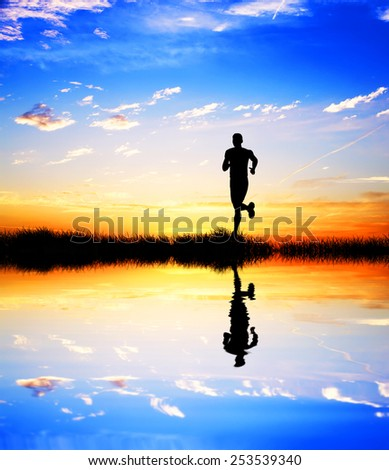 man running by the lake - stock photo