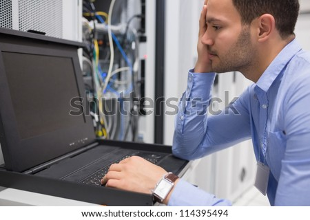 Man running diagnostics of servers in data center - stock photo