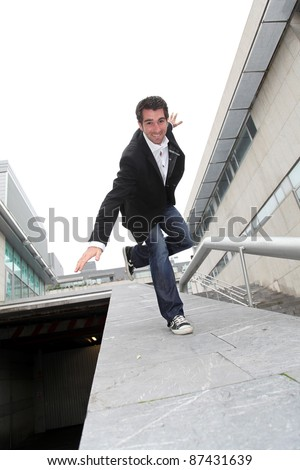 Man running downstairs with stretched arms - stock photo