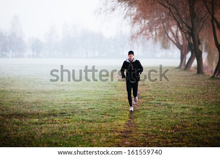Man running during foggy weather at winter or autumn morning. - stock photo