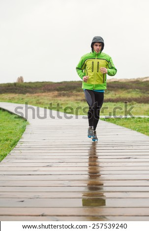 Man running in a winter rainy day. Photo in vertical composition. - stock photo