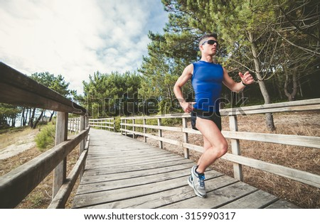 Man running in a wooden promenade in the forest