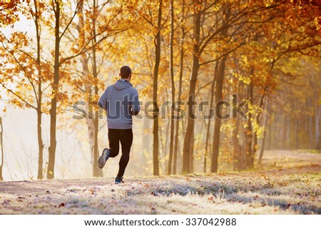 Man running in park during sunny autumn morning. Healthy lifestyle concept - stock photo