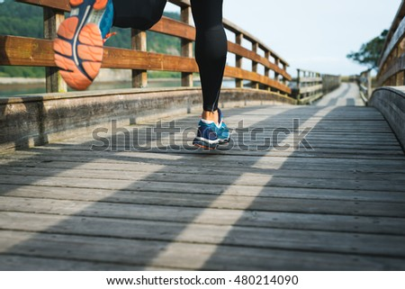man running in park on wooden walkway training and exercising for trail run marathon race. Fitness healthy lifestyle concept with male athlete outdoor runner. Rodiles, Asturias.