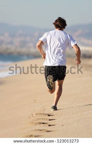Man running in the beach with his footprints back