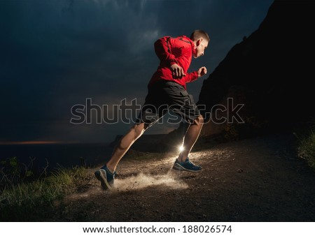 Man running in the mountains at night - stock photo
