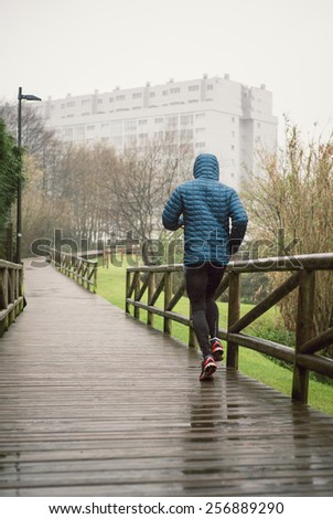 Man running in the park in a rainy day outdoors - stock photo