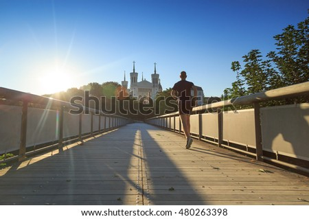 Man running near Basilica of Notre-Dame de Fourvière in Lyon on a sunny morning.
