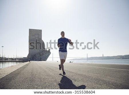 Man running next to Padrao dos Descobrimentos at Lisbon, Portugal - stock photo