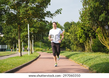 Man running on a track in a sunny day - stock photo