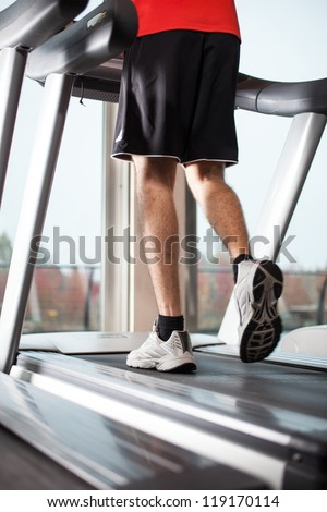 Man running on a treadmill in a fitness club