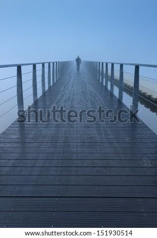 Man running on an foot- and bike bridge in the dense fog. - stock photo